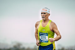Elderly male runner running. Omsk, Russia -  September 20, 2015: elderly male runner running during Siberian international marathon. background of sky Stock Images