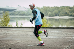 Elderly male runner runs along river Stock Photos