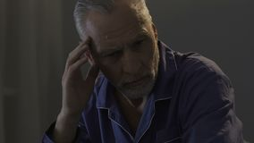 Elderly male sitting on bed in dark room, rubbing his temples, strong headache