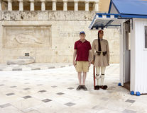 Elderly male tourist standing by a Gaurd. A soldier stands perfectly still in official uniform during the changing of the guards ceremony in Syntagma Square in Royalty Free Stock Photos