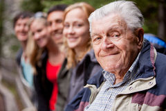 Elderly Man. An elderly man in front of a group of young people stock images