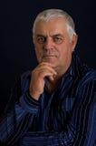 An elderly man. Portrait of an elderly man on a dark background Royalty Free Stock Photos