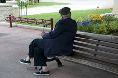 Elderly man 2. Elderly man with a cane sitting on a bench passing the time Stock Images