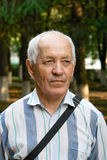 Elderly man. Portrait of the elderly man in a striped shirt against the nature Stock Image