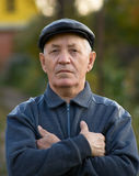 Elderly man. Portrait of the elderly man in a cap against the nature Stock Photography
