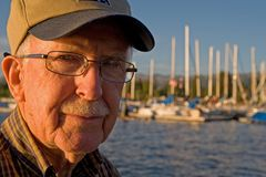 Elderly man. Portrait of a senior man in cap, with sailboats in the background royalty free stock image