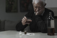 Elderly man addicted. To alcohol and drugs Stock Photography