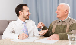 Elderly man and agent rent apartments. Old men and agent sign contract of rent apartments and hand over keys stock image