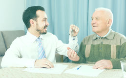 Elderly man and agent rent apartments. Retired and young men signed contract of rent apartments and hand over keys stock image