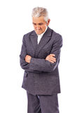 Elderly man with arms folded looking down lost in deep thought Stock Photos