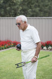 Elderly Man Carrying Artificial Bowling Arm and Ball. Royalty Free Stock Photos