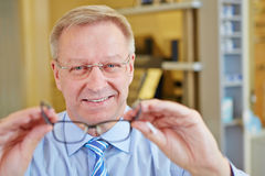 Elderly man as optician Stock Photography