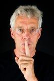 Elderly man asking for silence Stock Photography