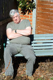Elderly man asleep sitting on bench. Royalty Free Stock Photo