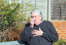 Elderly or old man with asthma inhaler. An elderly or old man outdoors having problem breathing and using an asthma inhaler for relief