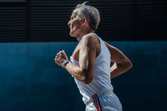 Elderly man athlete running on a city street Royalty Free Stock Photography