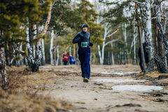 Elderly man athlete running on track  forest. Chelyabinsk, Russia -  April 3, 2016: elderly man athlete running on track  forest during Spring half marathon Royalty Free Stock Images
