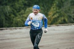 Elderly man athlete runs along waterfront Stock Photography