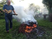 Elderly man with autumn bonfire. Gardening in autumn or fall - burning old cut off branches and leaves at garden bonfire. Elderly man smiling, bringing more logs stock image