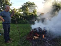Elderly man with autumn bonfire. Gardening in autumn or fall - burning old cut off branches and leaves at garden bonfire. Elderly man smiling, standing with a royalty free stock photos