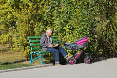 An elderly man with a baby in stroller sits in a park and reads a book stock photography