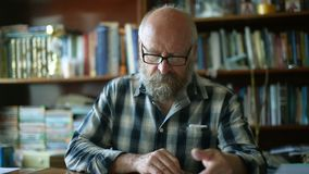 Elderly man thumbs a book. An elderly man with a bald spot on his head flips through an old book stock video footage