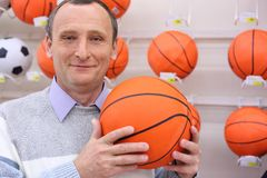 Elderly man with basketball ball. Elderly man in shop with basketball ball in hands stock photos