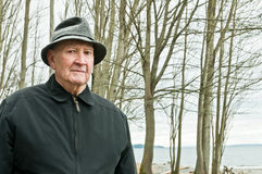 Elderly Man on Beach with Trees. Close up portrait of an older white male wearing a grey tweed rain hat and black jacket and standing on a wooded winter beach Stock Photography