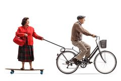 Elderly man on a bicycle pulling an elderly woman on a longboard. Elderly men on a bicycle pulling an elderly women on a longboard isolated on white background stock photo