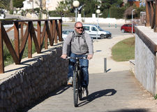 Elderly man on a bicycle. Royalty Free Stock Photo