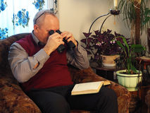 The elderly man with a binoculars in a chair royalty free stock image