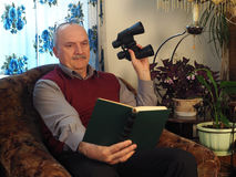 The elderly man with a binoculars in a chair royalty free stock photo