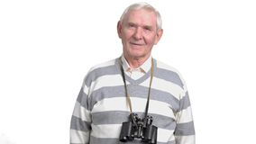 Elderly man with binoculars, white background. Senior male with binoculars round his neck looking at camera, isolated on white background stock footage