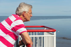 Elderly man on the boat. Elderly man is looking over the railing on the cruise boat royalty free stock images