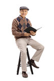 Elderly man with a book sitting on a chair. And looking at the camera isolated on white background Stock Images