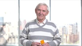 Elderly man with a bottle of pills. Pensioner holding container with medicine and looking at camera. Blood pressure has increased stock video footage