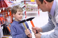 Elderly man with boy in shop with hammers Royalty Free Stock Photos