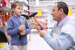 Elderly man with boy in shop with hammers Stock Photo