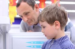 Elderly man with boy in shop look at refrigerator stock photo