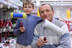 Elderly man with  boy in shop with rollers Royalty Free Stock Photography