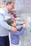 Elderly man with boy in store. Hang grill for roasting on wall royalty free stock images