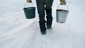 An elderly man with buckets in winter carries water from a well. Handheld shooting.