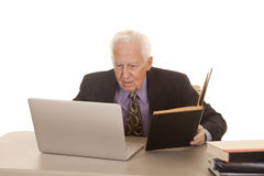 Elderly man business computer book. An elderly man in a suit and tie with a laptop and some books Royalty Free Stock Photo