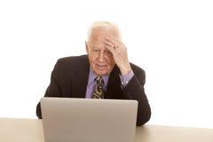Elderly man business computer hand on head. A old man with a computer has his hand on his forehead Stock Photos