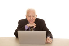 Elderly man business computer hand under chin. An old man sitting at a computer wearing a suit and tie Royalty Free Stock Photos