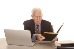 Elderly man business computer look at book. An elderly man with a laptop and some books in a suit and tie Royalty Free Stock Photos