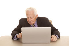 Elderly man business computer study. An elderly man sitting at a computer in a suit and tie Stock Photo