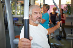 Elderly man on butterfly machine Stock Photography