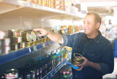 Elderly man buying preserves at the grocery store. Happy smiling elderly man buying preserves at the grocery store royalty free stock photo