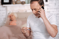 Elderly man calling emergency while checking thermometer Royalty Free Stock Photography